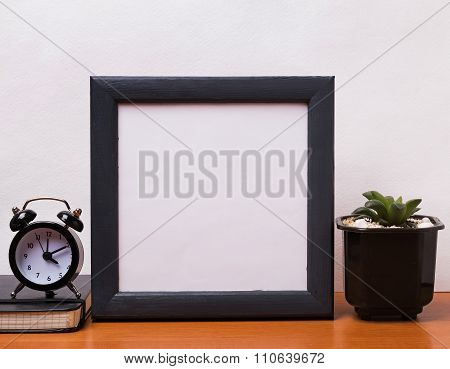 Blank Frame, Alarm Clock And Succulent Plant On The Table
