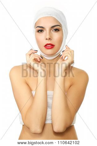 Young beautiful woman with a gauze bandage on her head and chest, isolated on white