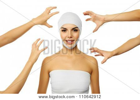 Young beautiful woman with an elastic bandage on the head and hands around her, isolated on white