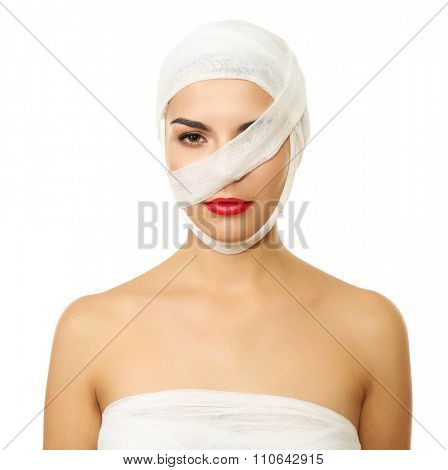 Young playful woman with a gauze bandage on her head and chest, on black background
