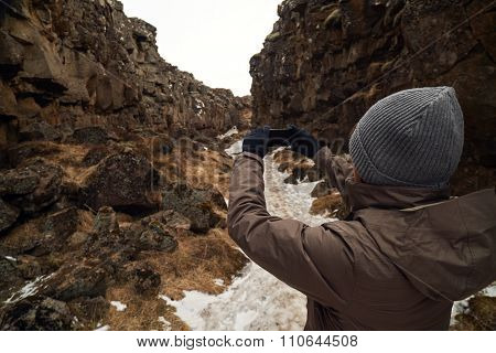 Tourist taking photso of the crack between tectonic plates in Pingvellir national park Iceland