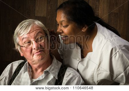 Nurse in a home talking loudly to a hearing impaired elderly man