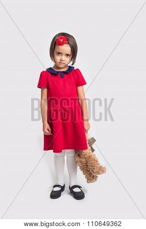 Unhappy beautiful little girl in a red dress with a toy bear
