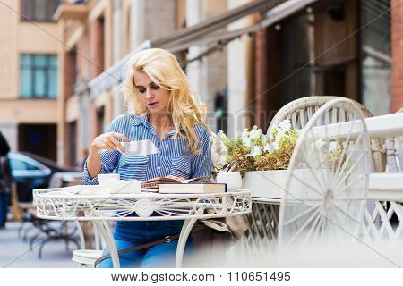 Young carefree lady reading letter while relaxing in coffee shop after walking outdoors