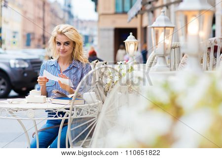 Amazing blonde Caucasian woman posing while sitting with book in coffee shop in the fresh air