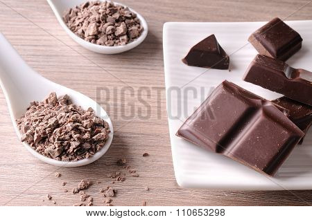 Portions And Chocolate Chips On White Container On Wood Table