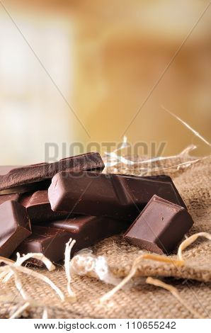 Heap Of Artisan Portions Chocolate On Burlap Front View Vertical