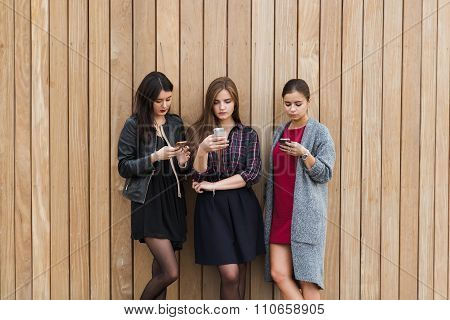 Charming hipster girls dressed with style using telephone