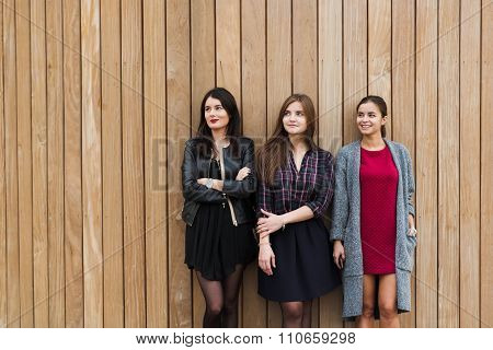 Group of charming stylish hipster girls standing on wooden wall background