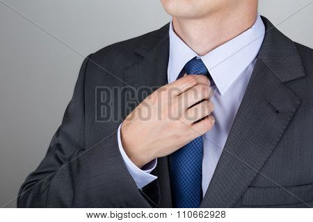 Well Dressed Business Man Adjusting The Necktie