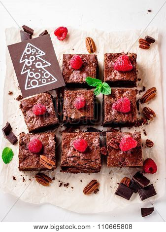 Brownie Pieces With Nuts Decorated With Berries And Mint Leaves On The White Paper.