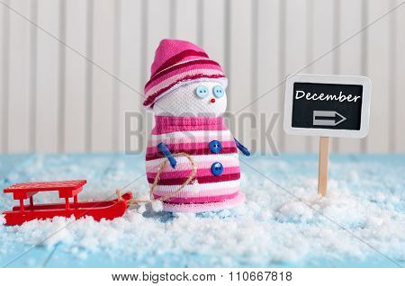 Word December written on direction sign and Snowman with red sled. Christmas, New year decorations.