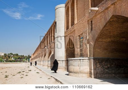 Women Walk Along The Stone Cross Dried River, Iran