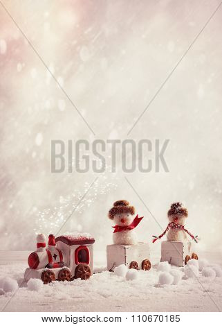 Toy train set carrying snowmen in winter setting with vintage tone - plenty of copy space for text