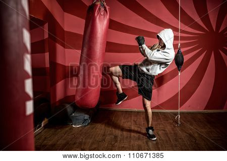 Boxer and athlete training and practicing kicks in the gym