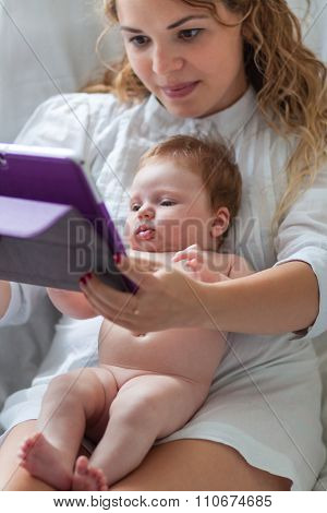 Newborn girl using tablet