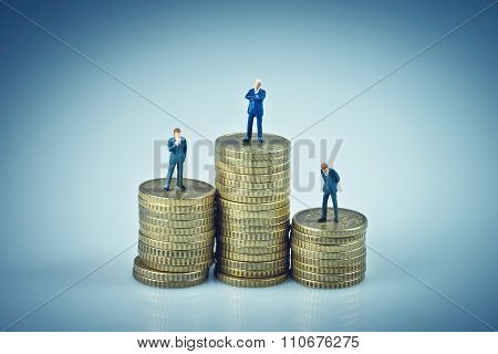 Financial concept. Business people standing on coins piles. Macro photo