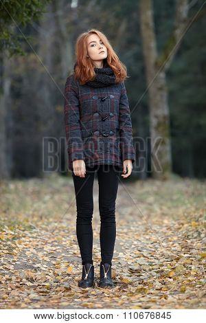 Full length young trendy redhead woman in scarf and plaid jacket on forest path