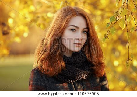 Young beautiful redhead woman in scarf and plaid jacket against autumn foliage background