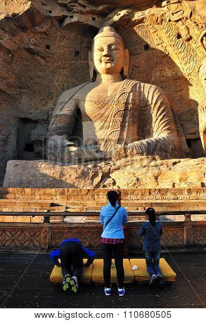 Unidentified visitors praying in front of Buddha Statue
