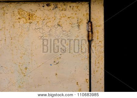 Rusty metal door and hinge on it.