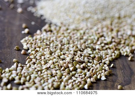 closeup of a pile of uncooked buckwheat seeds on a rustic wooden surface