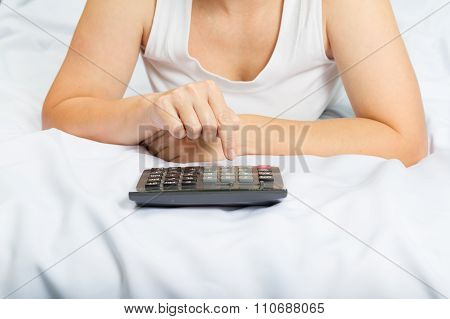 Young Woman In Bed With A Calculator. Family Budget. Credit,