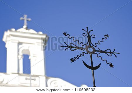 Closeup Of Black Metal Cross With A White Church In The Background