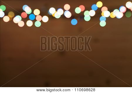 Blur background and bokeh of Christmas light boarder on wooden background.