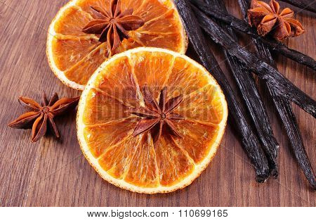 Fragrant Vanilla, Star Anise And Dried Orange On Wooden Surface Plank