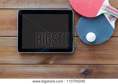 sport, technology, game and objects concept - close up of ping-pong or table tennis rackets with ball and tablet pc computer on wooden floor