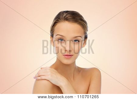 beauty, people, body care and health concept - smiling young woman face and hand on bare shoulder over beige background