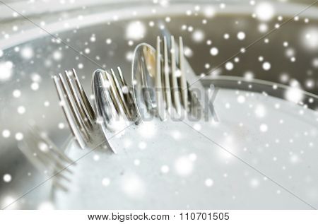 housework, washing-up and housekeeping concept - close up of dirty dishes washing in kitchen sink over snow effect