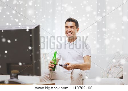 home, people, technology and entertainment concept - smiling man with remote control watching tv and drinking beer at home over snow effect