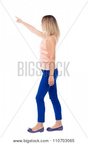 back view of pointing walking  woman. going girl pointing.  backside view of person.  Rear view people collection. Isolated over white background. The blonde leaves left in a pink t-shirt.