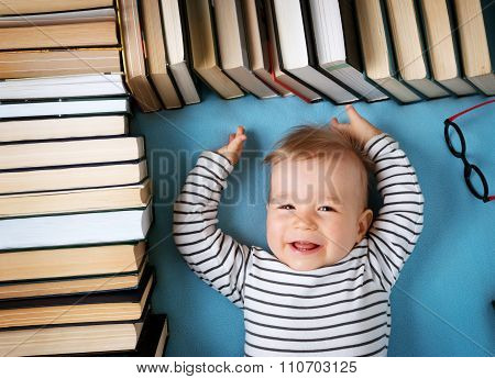 One year old baby with spectackles and books