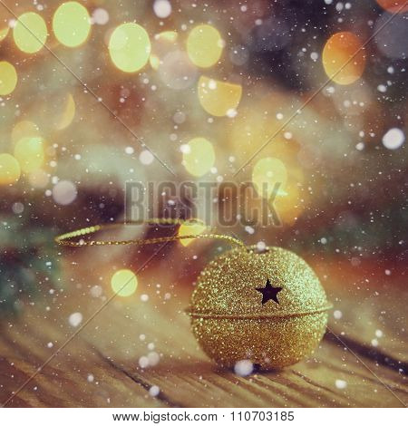 Metal Gold Jingle Bell With Star On Wooden Table With Snow. Chri
