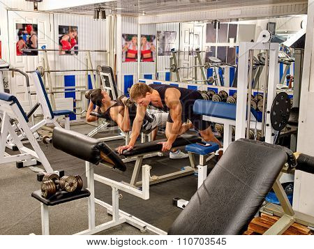 Group of men working on simulator his body at gym with mirror and picture on wall.