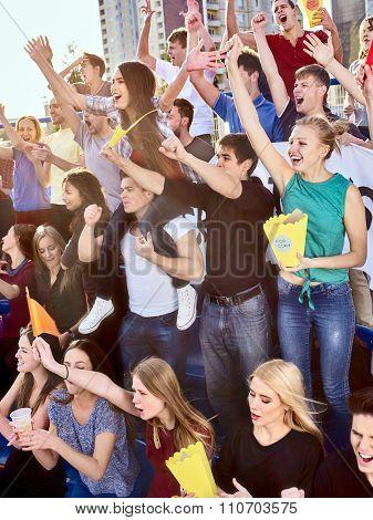 Sport fans hands up eating popcorn  and singing on tribunes. Group people.