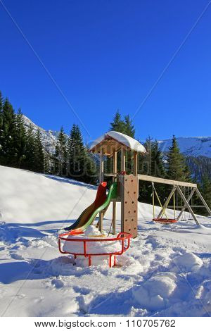 A roundabout, swing, playground slide covered in snow during the winter in Austria
