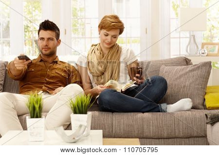 Young couple sitting at home on sofa. Woman reading, man watching TV, holding remote control.