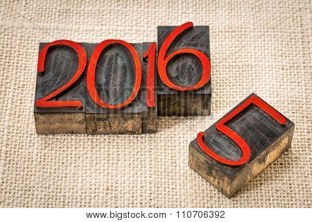 new year 2016 replacing the old year 2015 - letterpress wood type stained by red ink on a burlap canvas