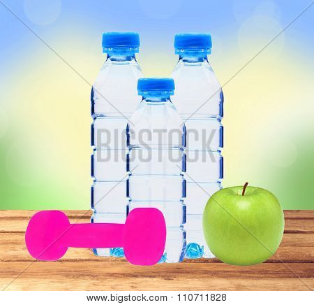 Blue Bottles With Water, Dumbell And Green Apple On Table Over Nature Background