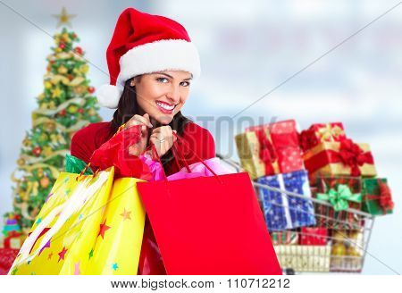 Happy Santa Christmas woman with bags over X-mas Tree background.