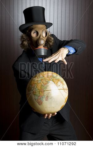 Man wearing a gas mask holding an earth globe