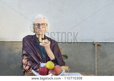 Old Woman Having A Snack In The Backyard