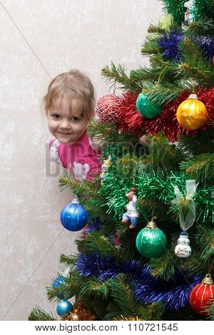 Little Girl Peeking Out From Behind Christmas Tree