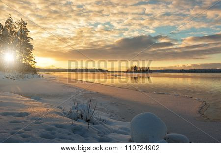 A Beautiful Winter Landscape By The River At Sunset With A Snowdrift In The Foreground And The Islan