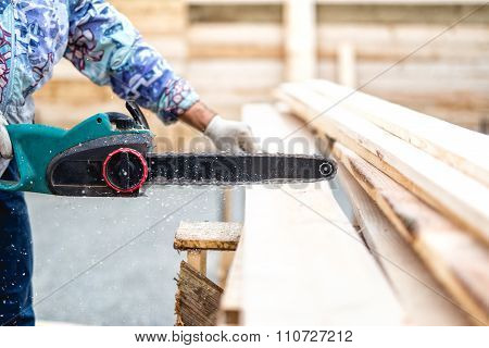 Worker, Lumberjack Or Handyman Cutting Timber Planks With Electric Chainsaw