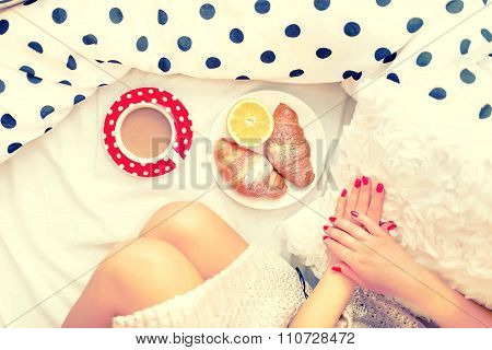 Close-up Of Woman Legs And Breakfast In Bed With Croissants, Coffee And Orange Juice